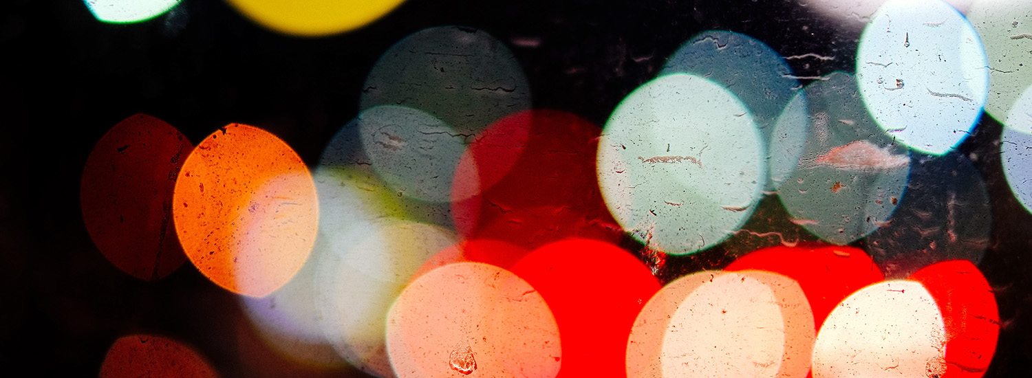 Colored dots produced by light through raindrops.