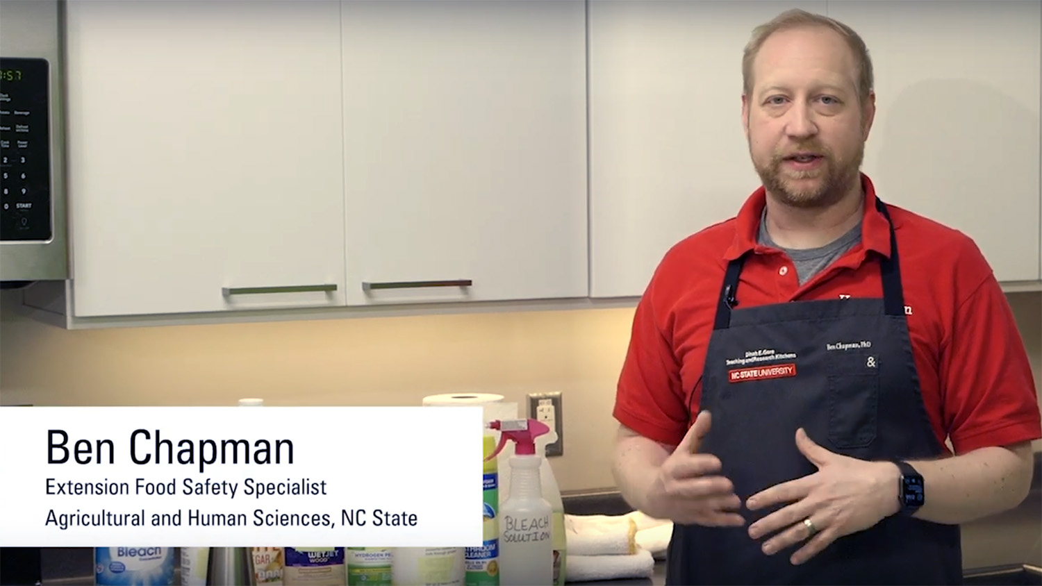A still from a video showing Ben Chapman in an apron as he explains how to sanitize surfaces.