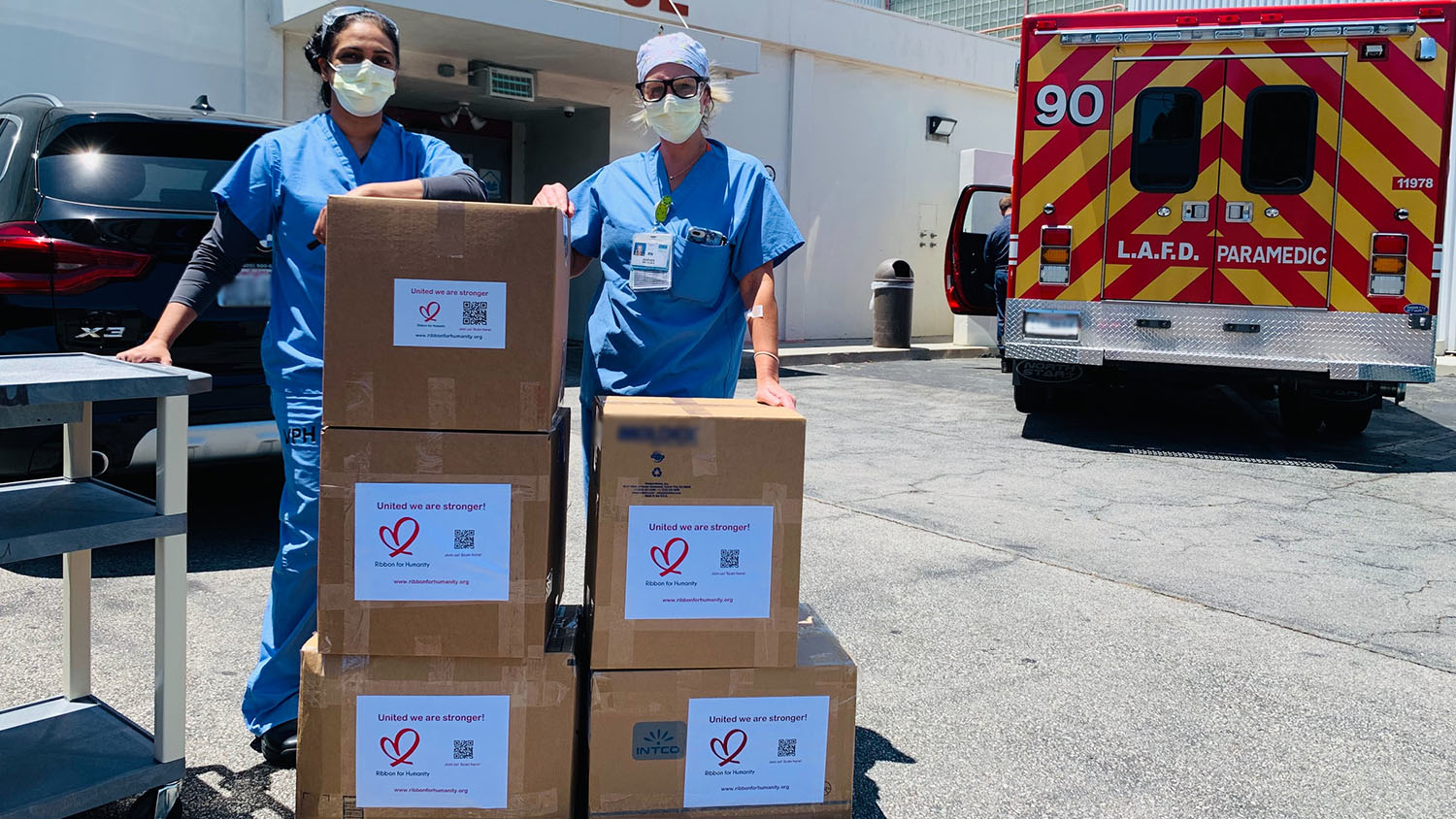 nurses stand with newly-delivered boxes of PPE