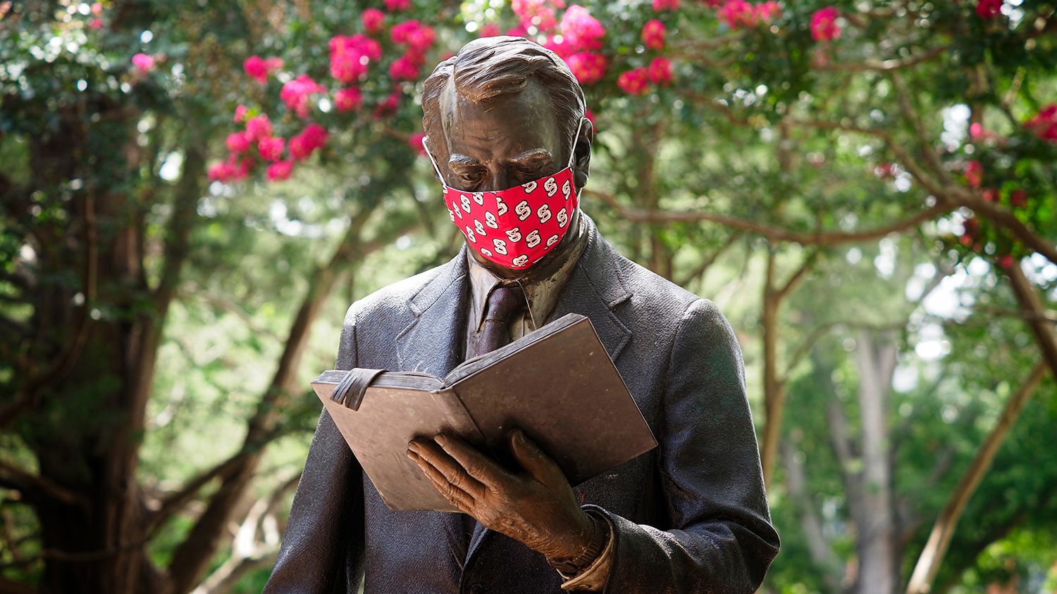 The strolling professor statue dons a protective mask
