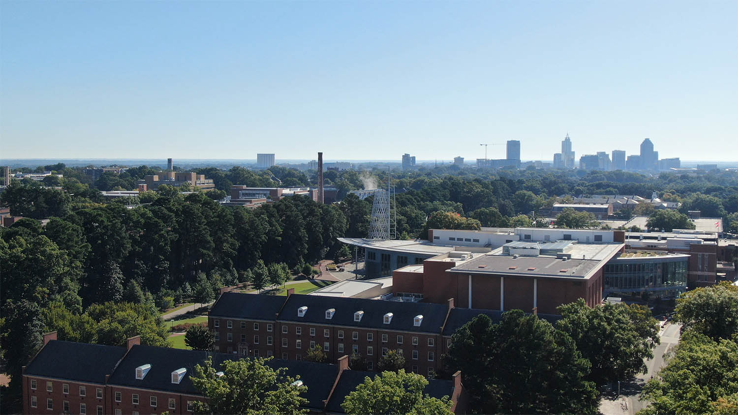 An aerial view of brick buildings and Talley Student Union, with downtown Raleigh in the background