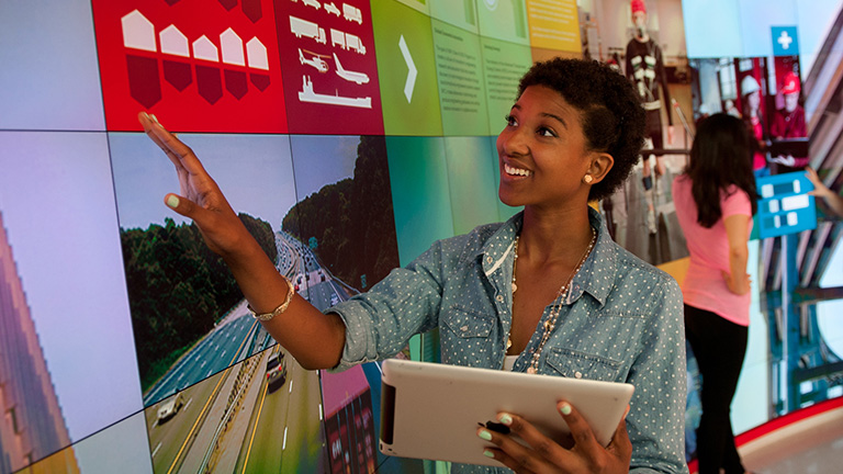 Woman using big, tiled screen while holding an iPad