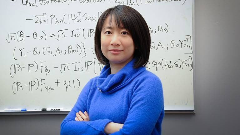 Assistant Professor Rui Song, who works in the NC State Department of Statistics, stands with her arms folded in front of a whiteboard.