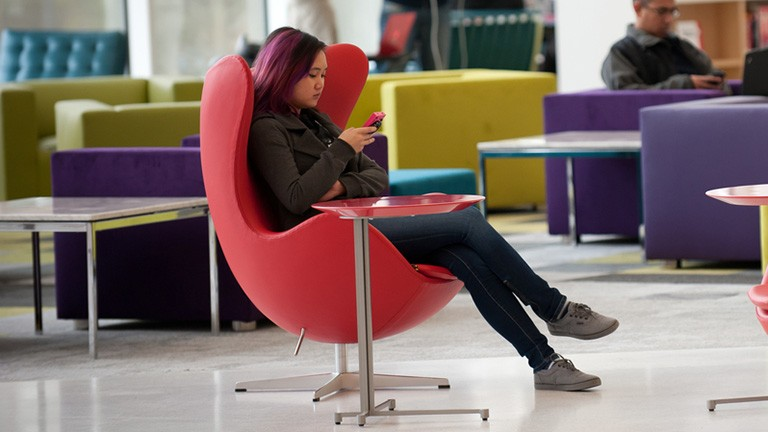 Girl sitting in red chair in Hunt Library using smartphone.