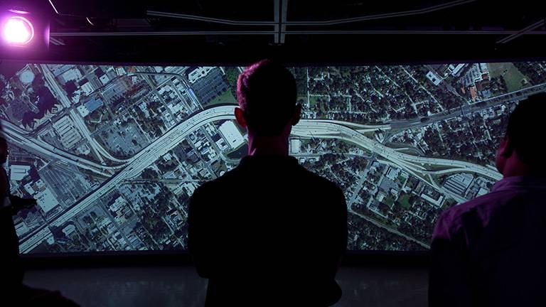 Person standing in front of large screen in Teaching and Visualization Lab