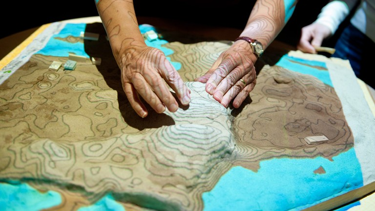 People working with topographic model