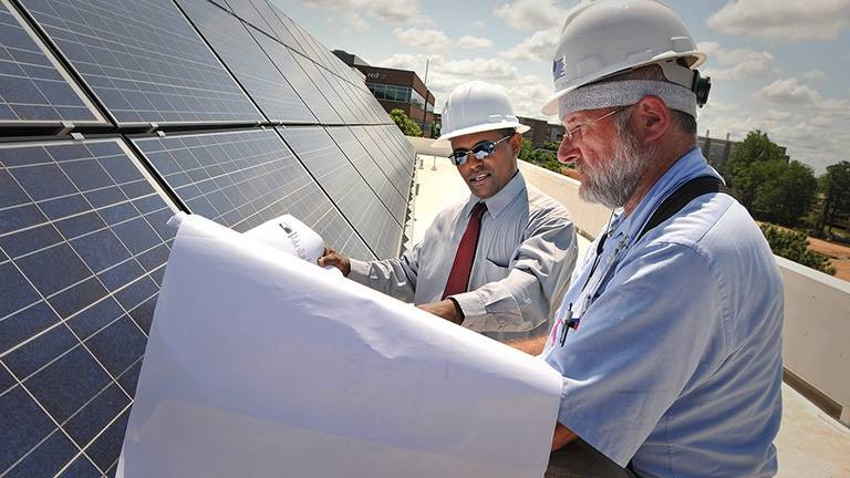 Two men looking at blueprints in front of solar panels