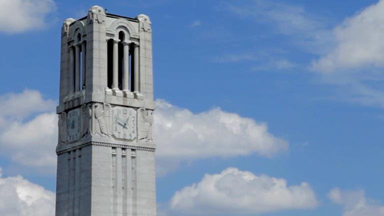 NC State's Memorial Bell Tower against a blue sky and cumulus clouds.