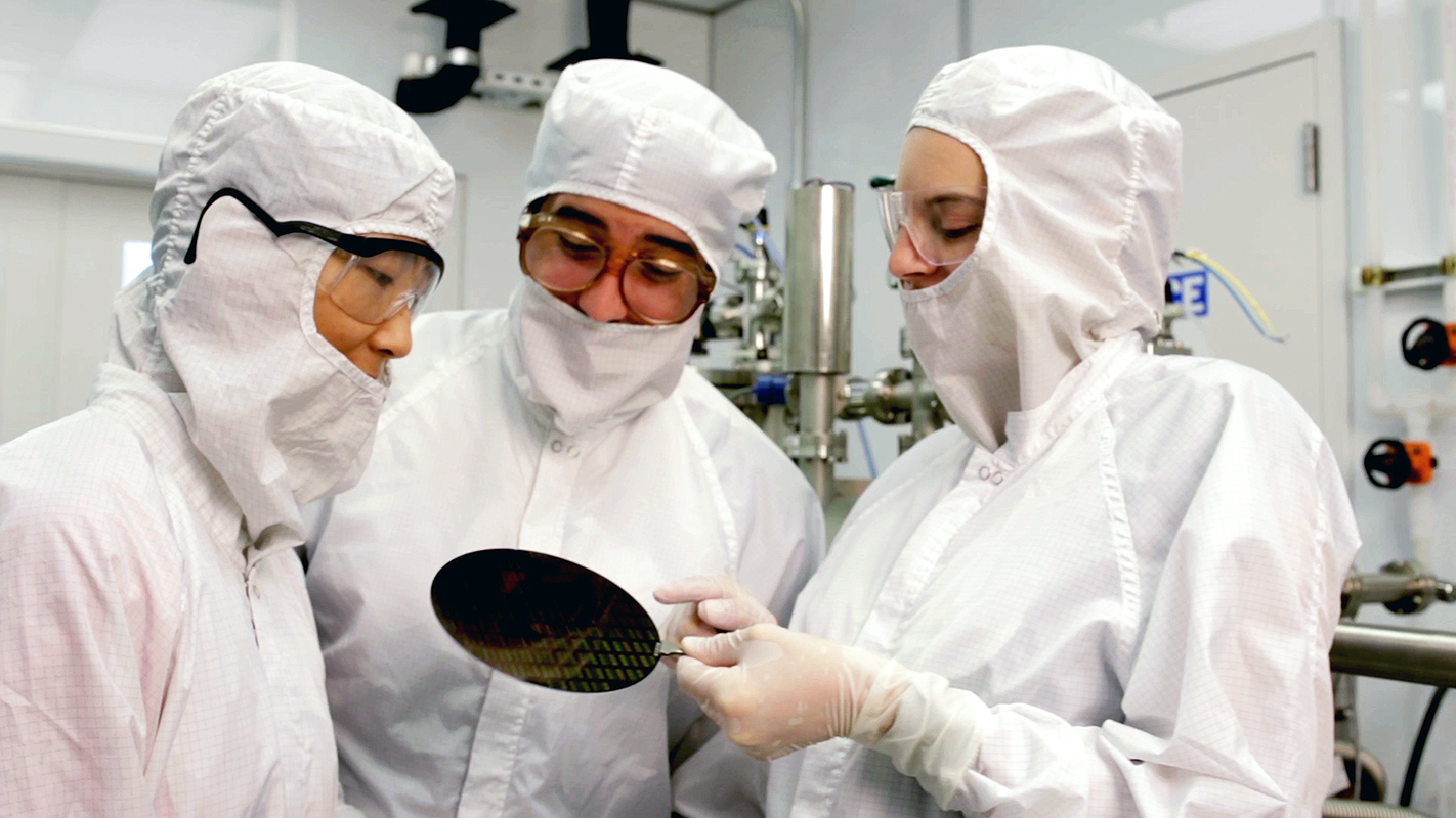Three NC State researchers examine a device in a clean room.