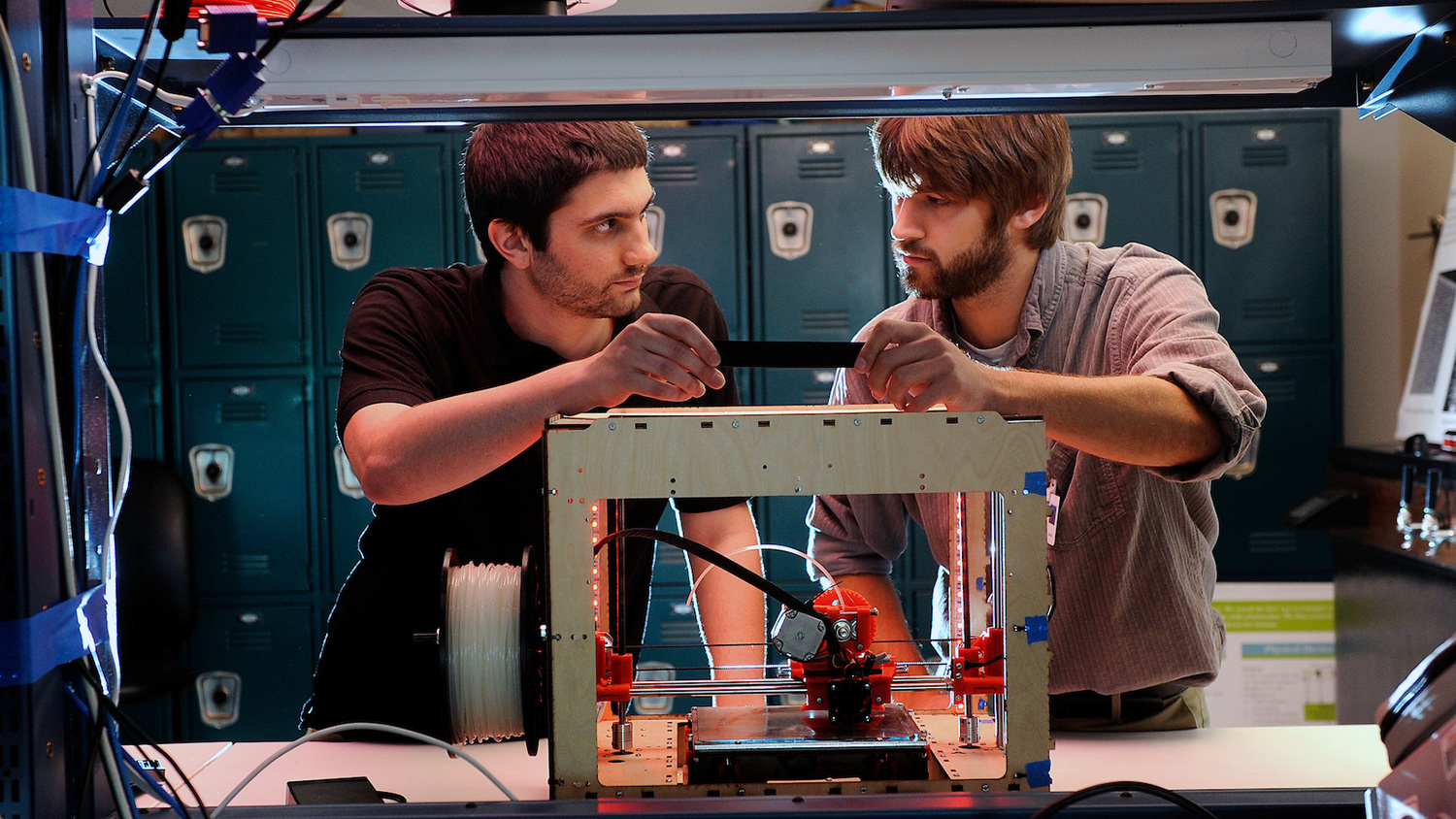 Two young men standing behind a 3-D printer.