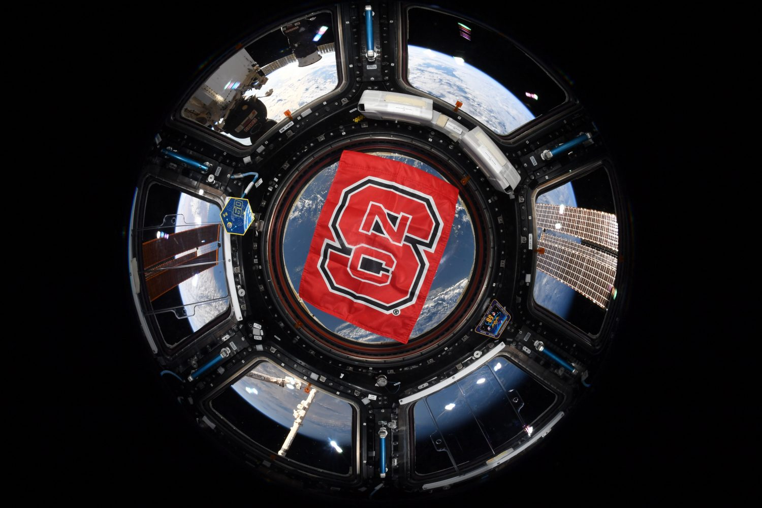 An NC State flag is displayed in the cupola of the International Space Station in orbit above the Earth.