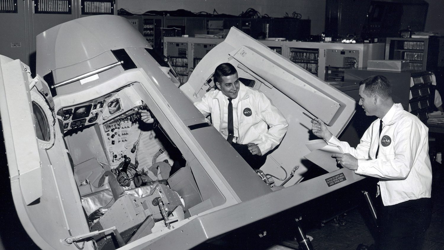 A black-and-white photo of two men working on a space shuttle capsule